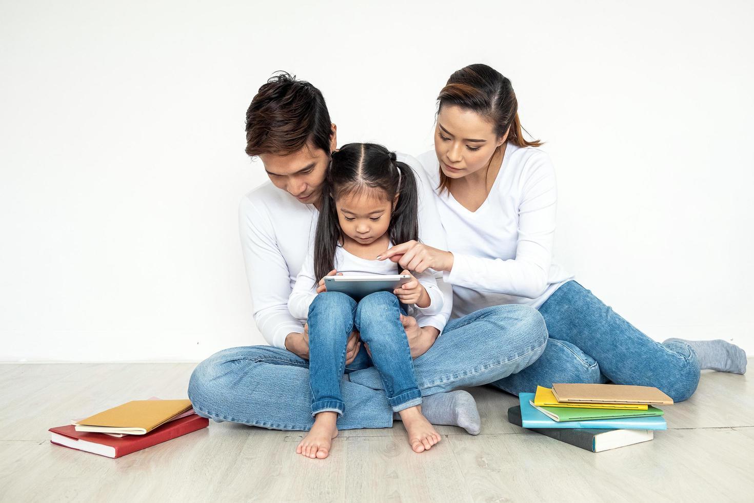 Aziatische familie die tablet samen gebruiken foto