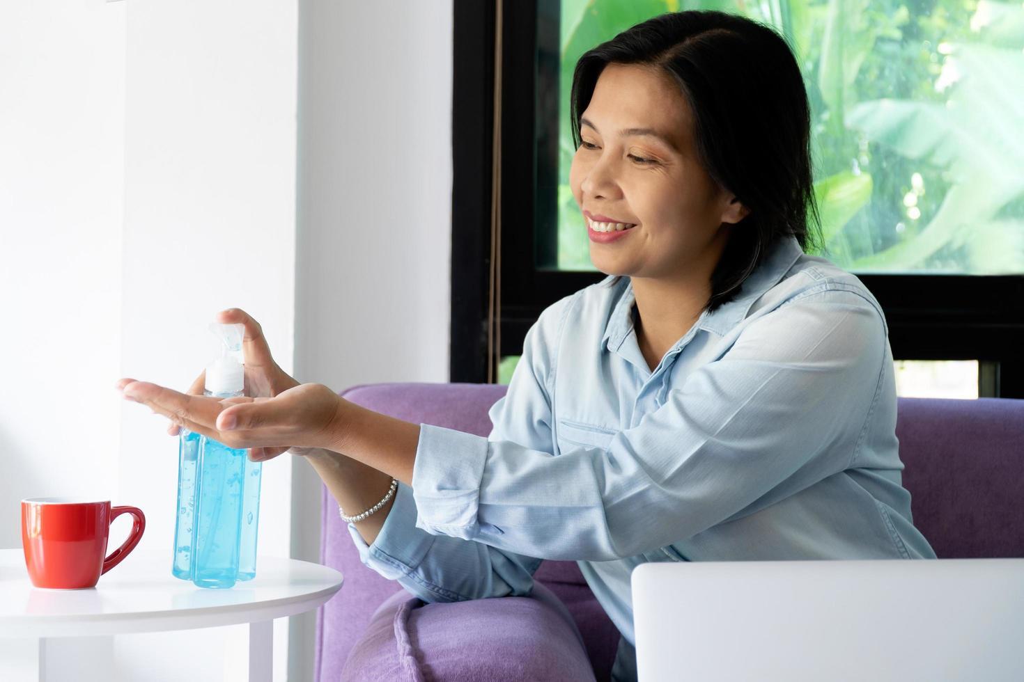 vrouw met handdesinfecterend middel foto
