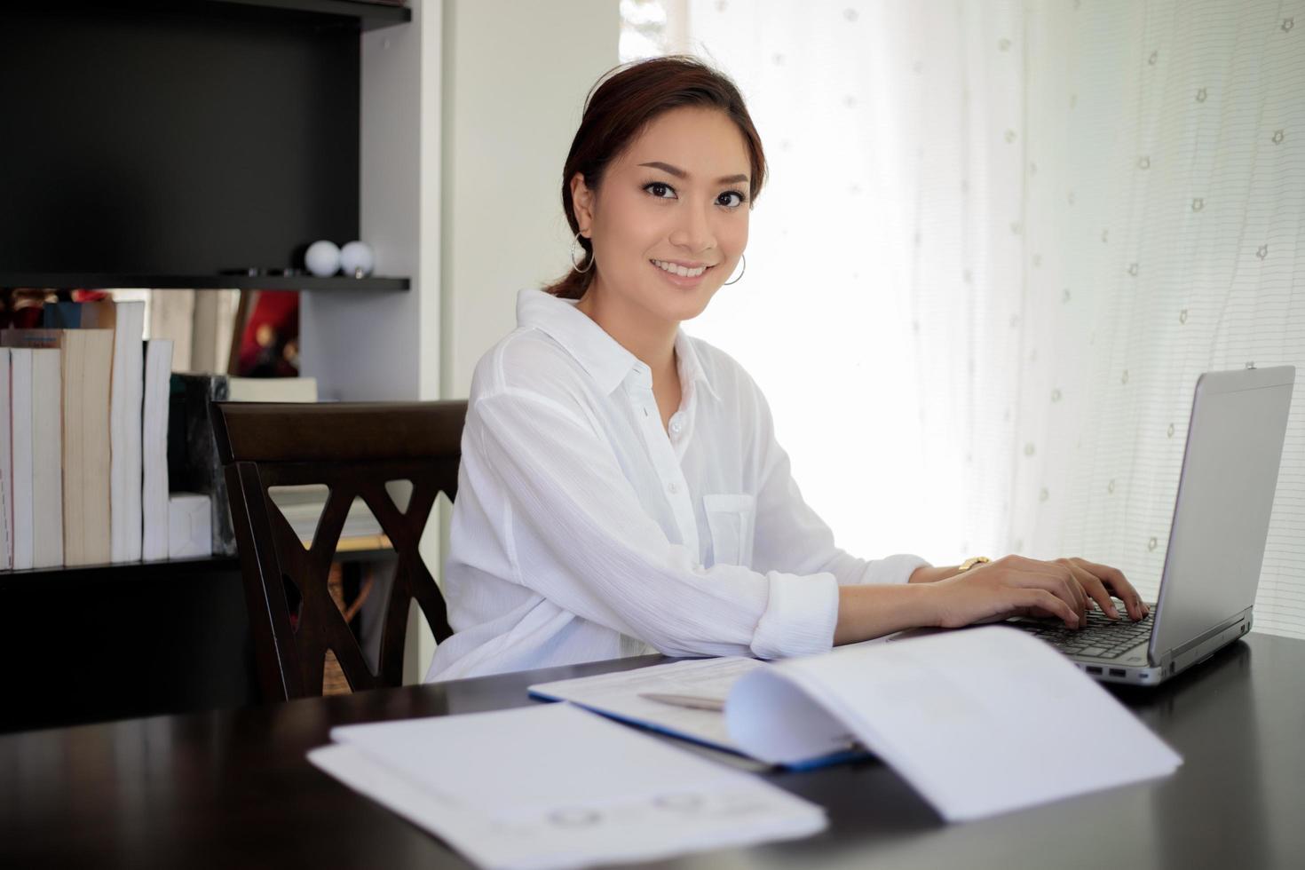 Aziatische zakenvrouw werkt in kantoor aan huis foto