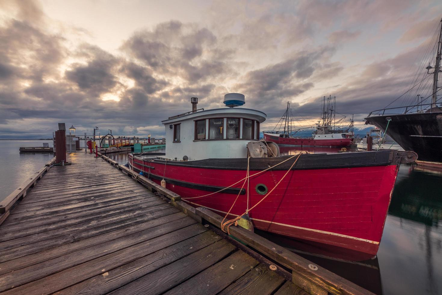 rode en witte boot op dok onder bewolkte hemel foto