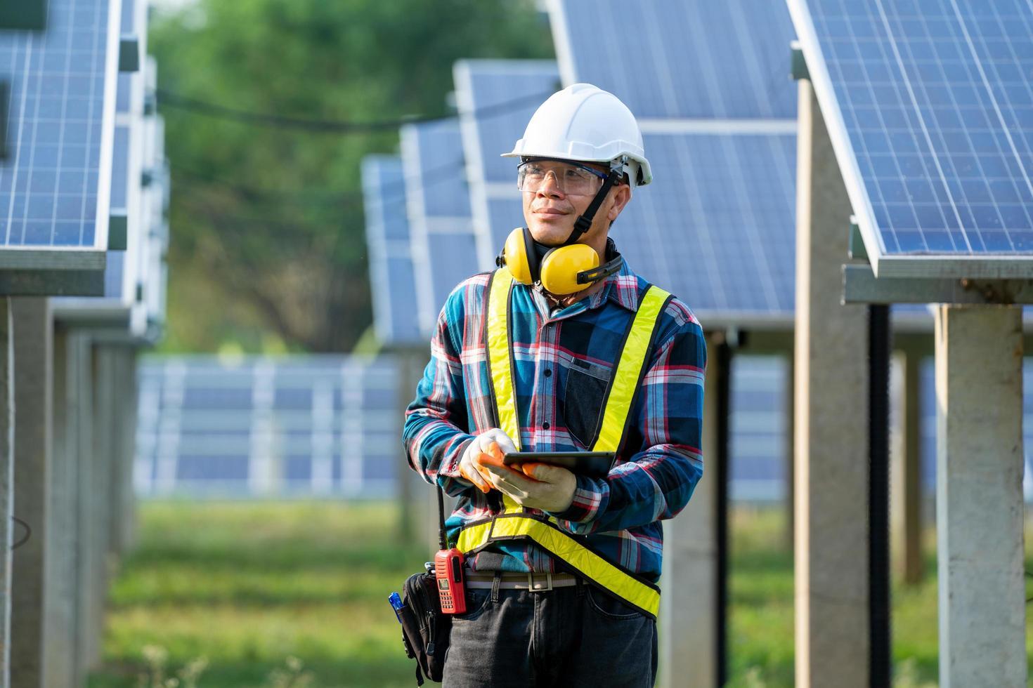 man met veiligheidsuitrusting naast zonnepanelen foto