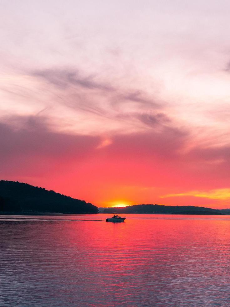 persoon op boot in water bij zonsondergang foto