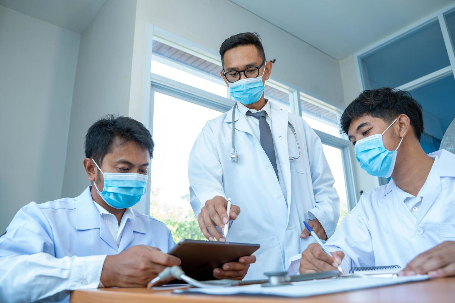 mannen met laboratoriumjassen en gezichtsmaskers foto