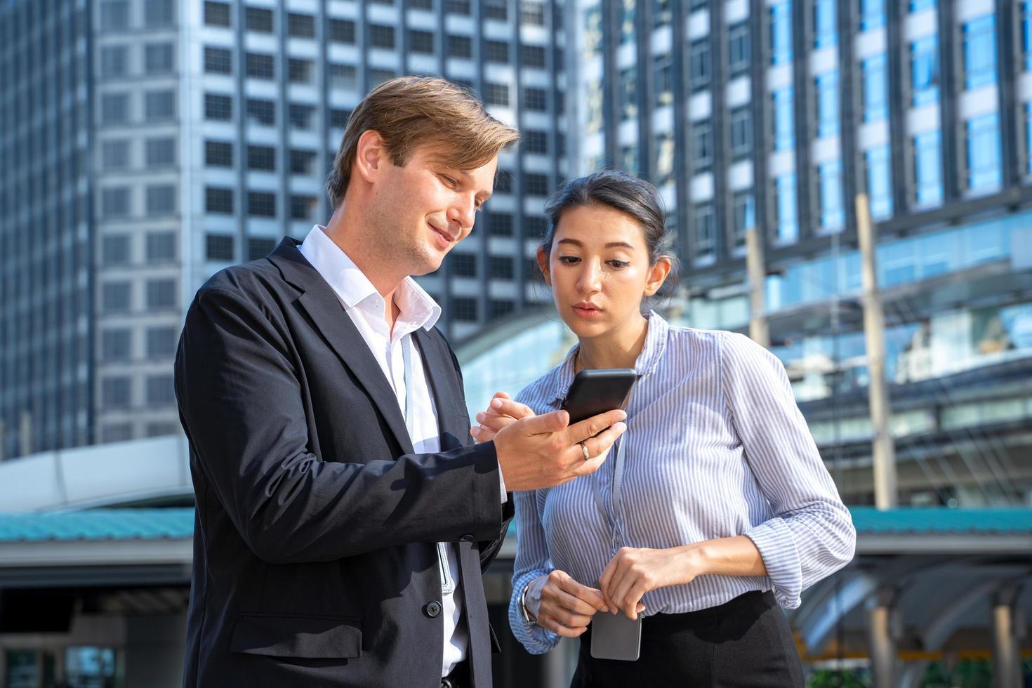 man en vrouw kijken naar mobiele telefoon foto