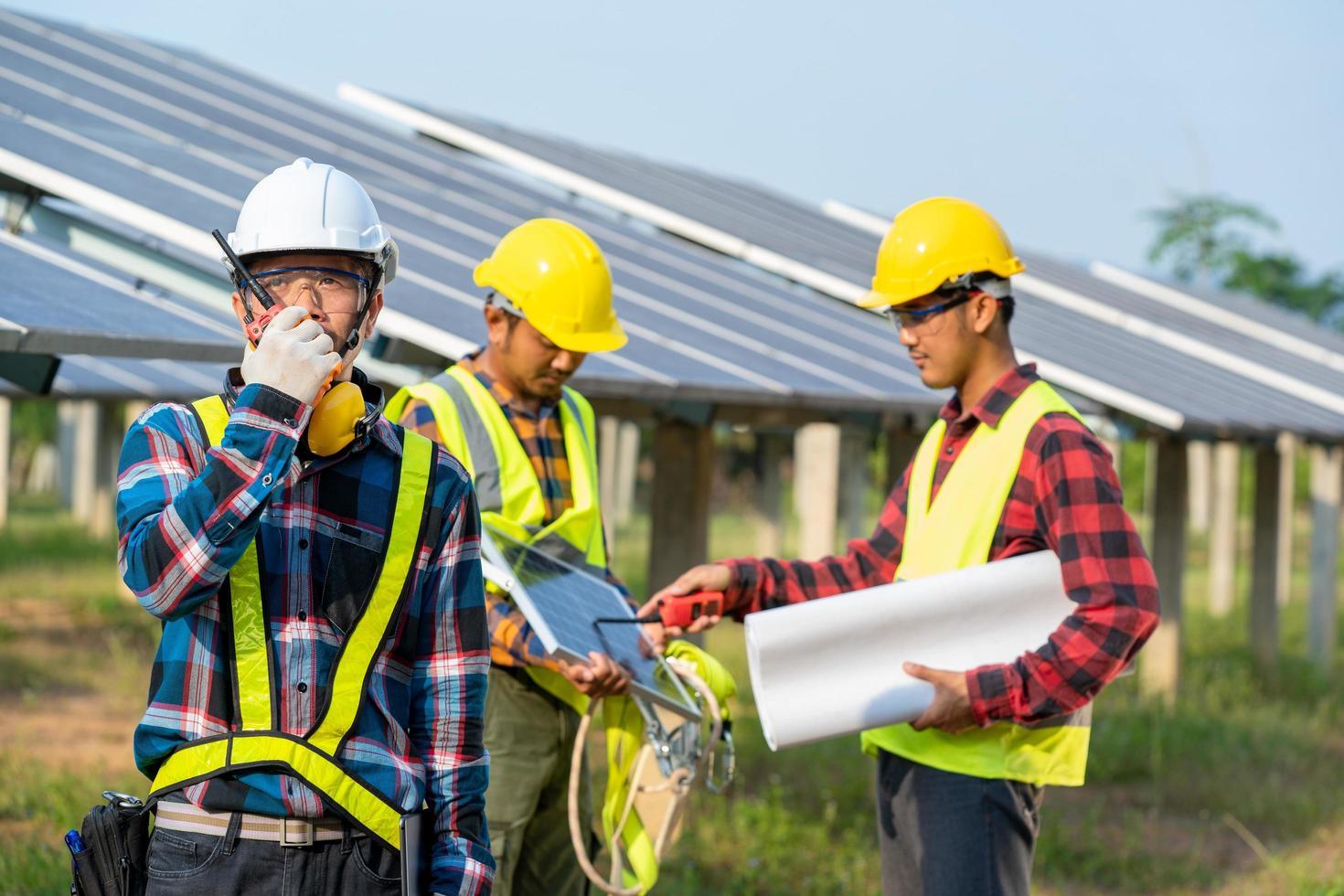 mannen met veiligheidsuitrusting naast zonnepanelen foto