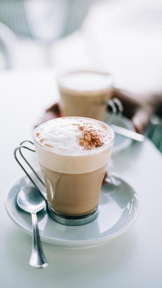 lattes in heldere mokken op schoteltjes foto