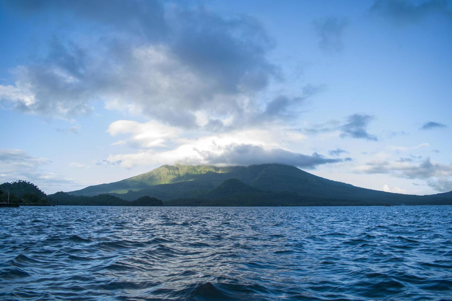 oceaan in de buurt van berg met wolken foto
