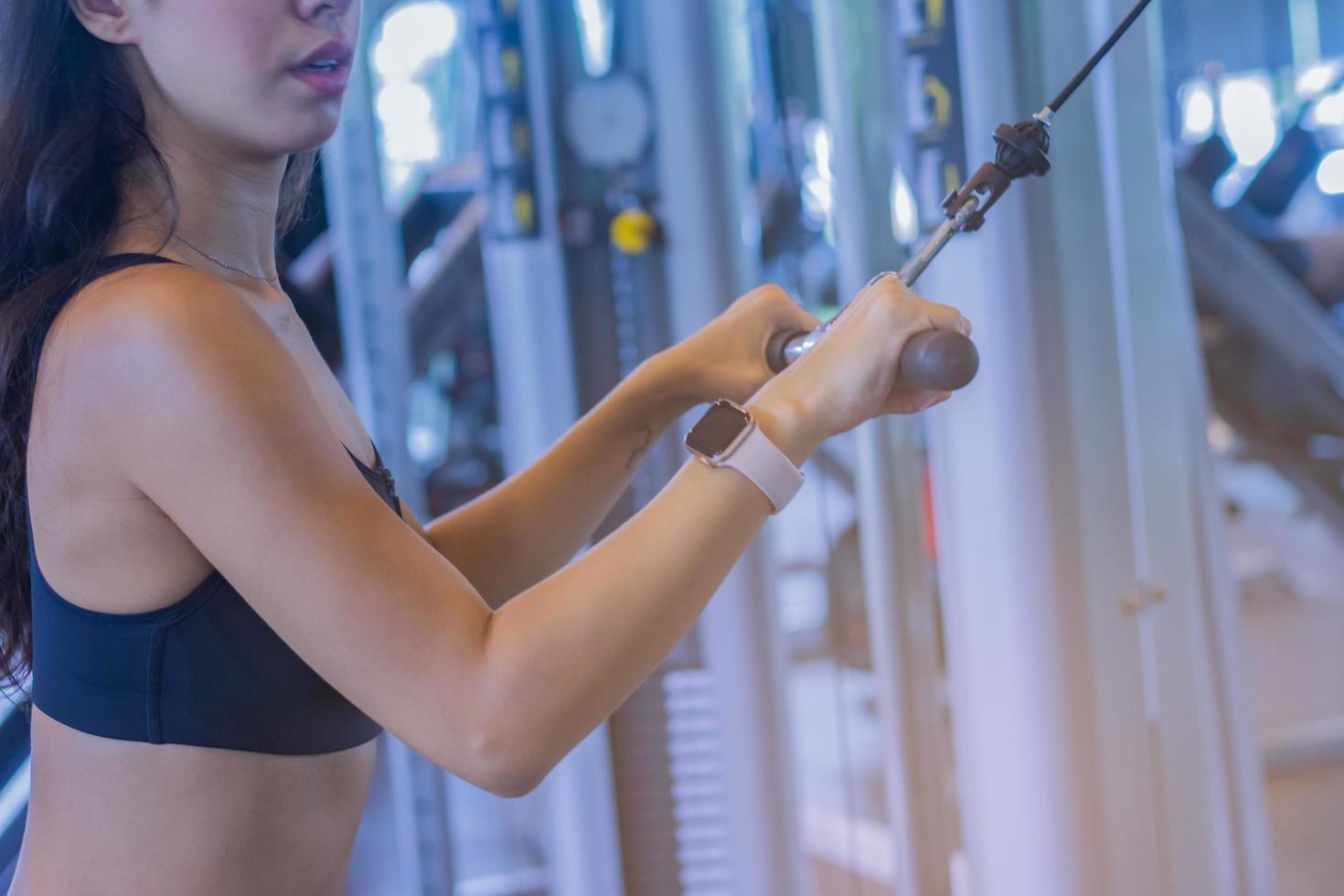 jonge mooie vrouw die oefeningen in de sportschool doet foto