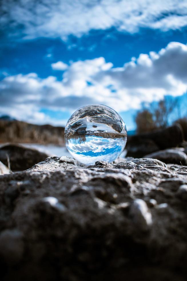 glazen bol op rotsen met blauwe hemel foto