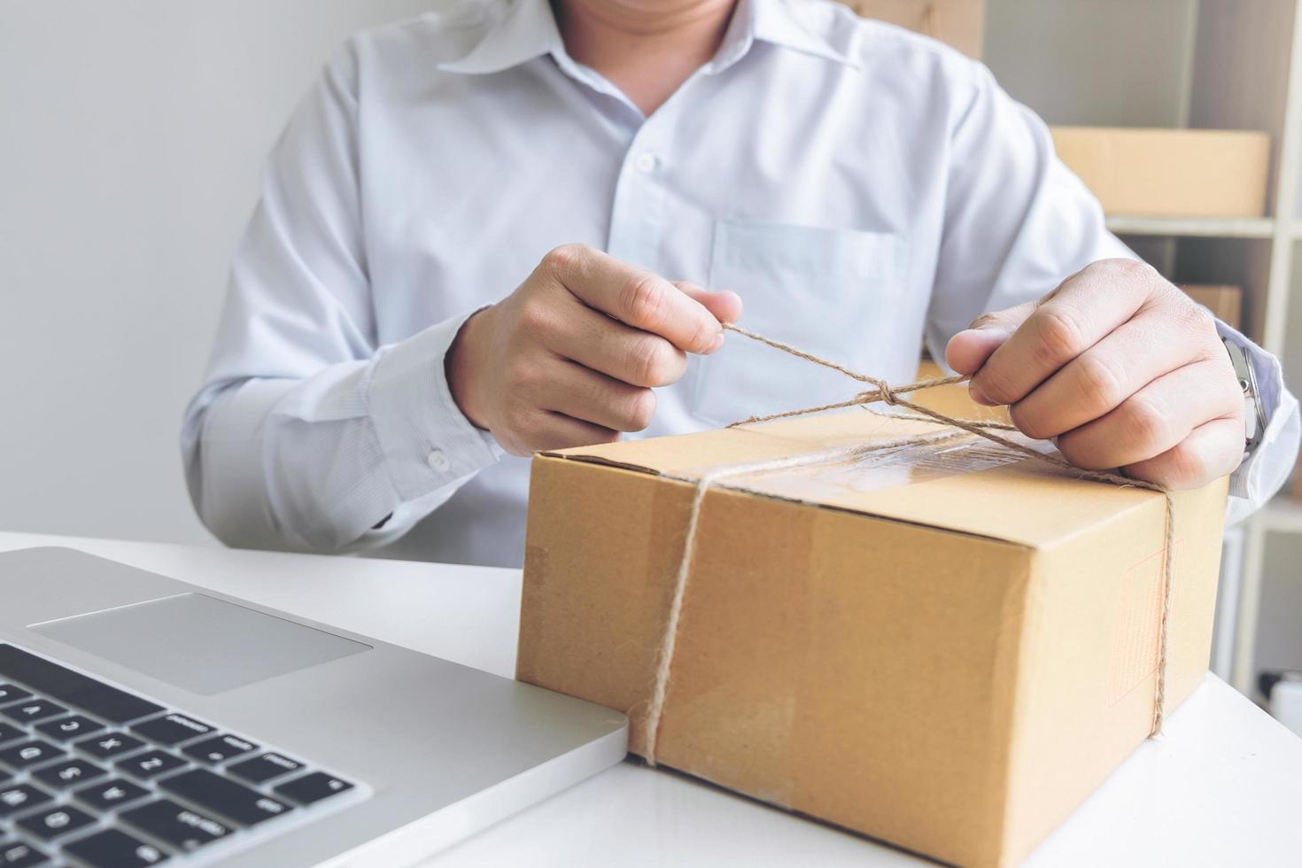 jonge verkoper die het te verzenden pakket voorbereidt foto