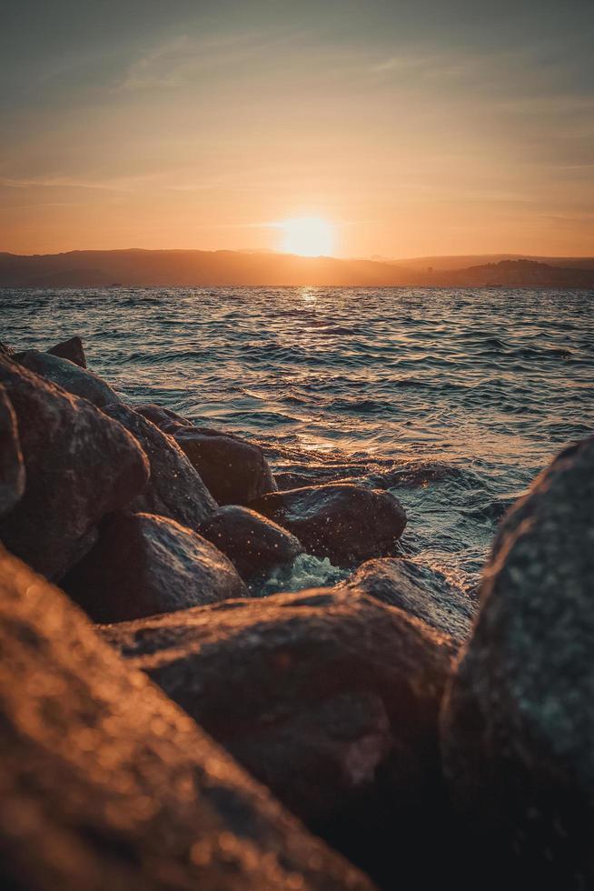 rotsachtige kust en water bij zonsondergang foto