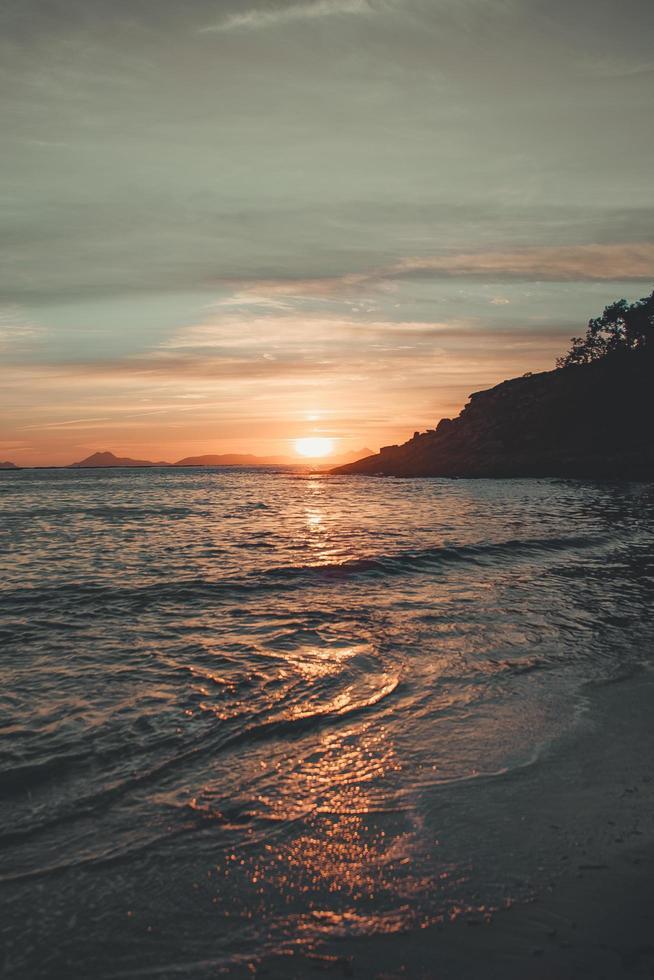 kleurrijke zonsondergang over bergen en strand foto