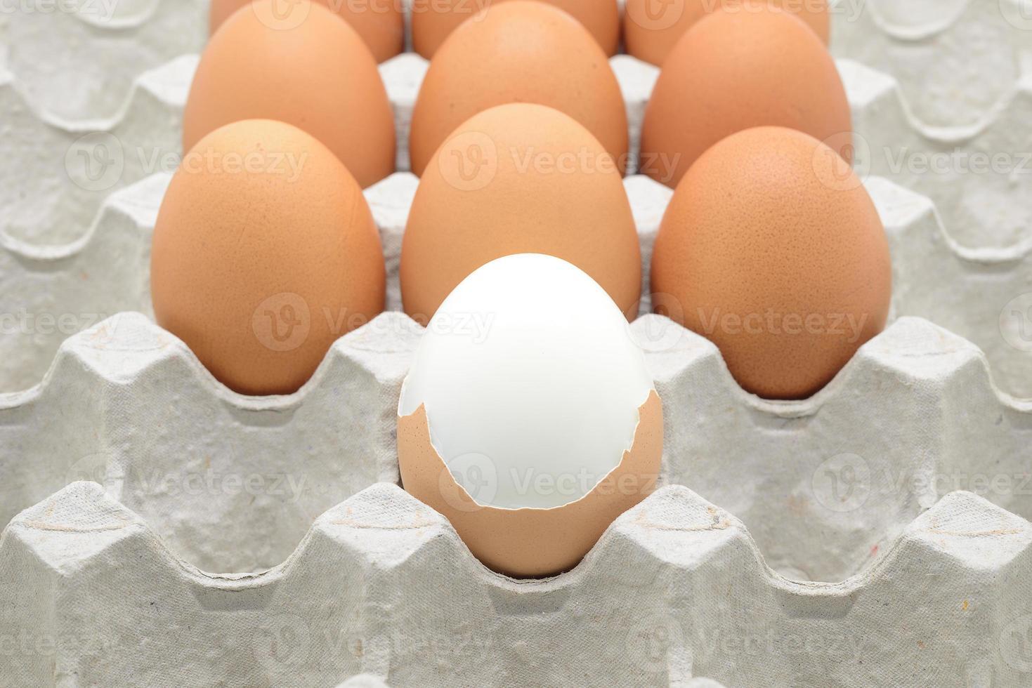 gekookt ei en rauwe eieren op een papieren krat foto