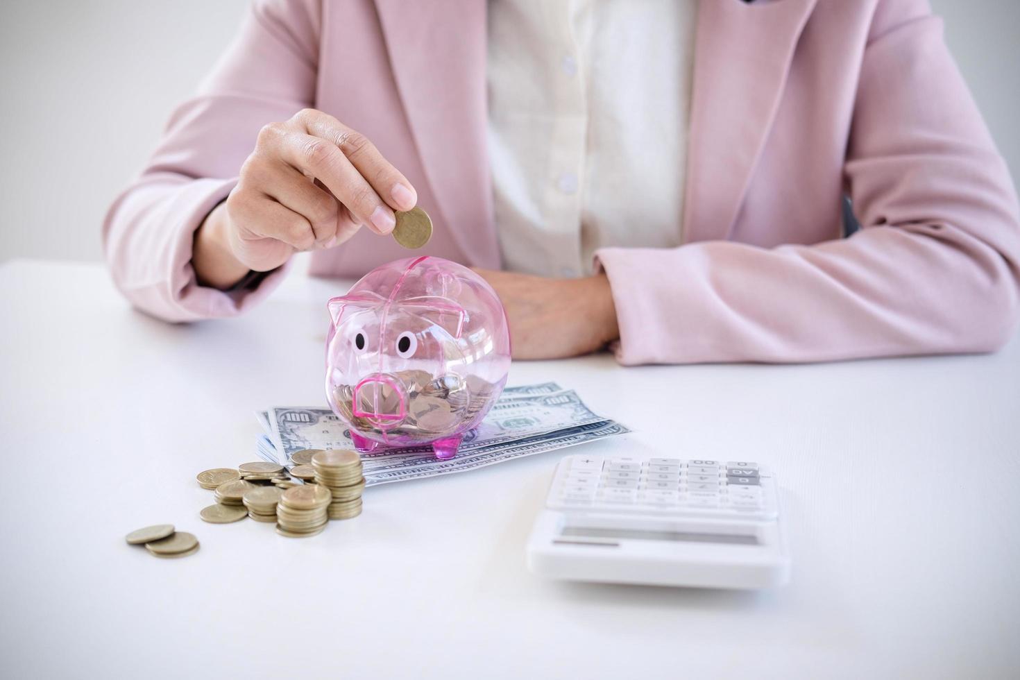 zakenvrouw munten ingebruikneming spaarvarken foto