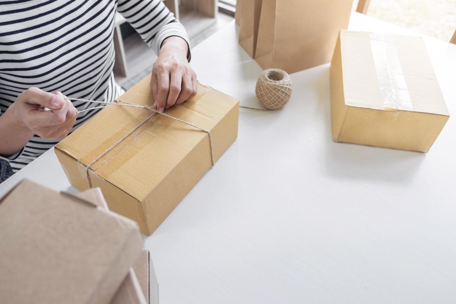 jonge verkopersvrouw die pakket voorbereiden foto