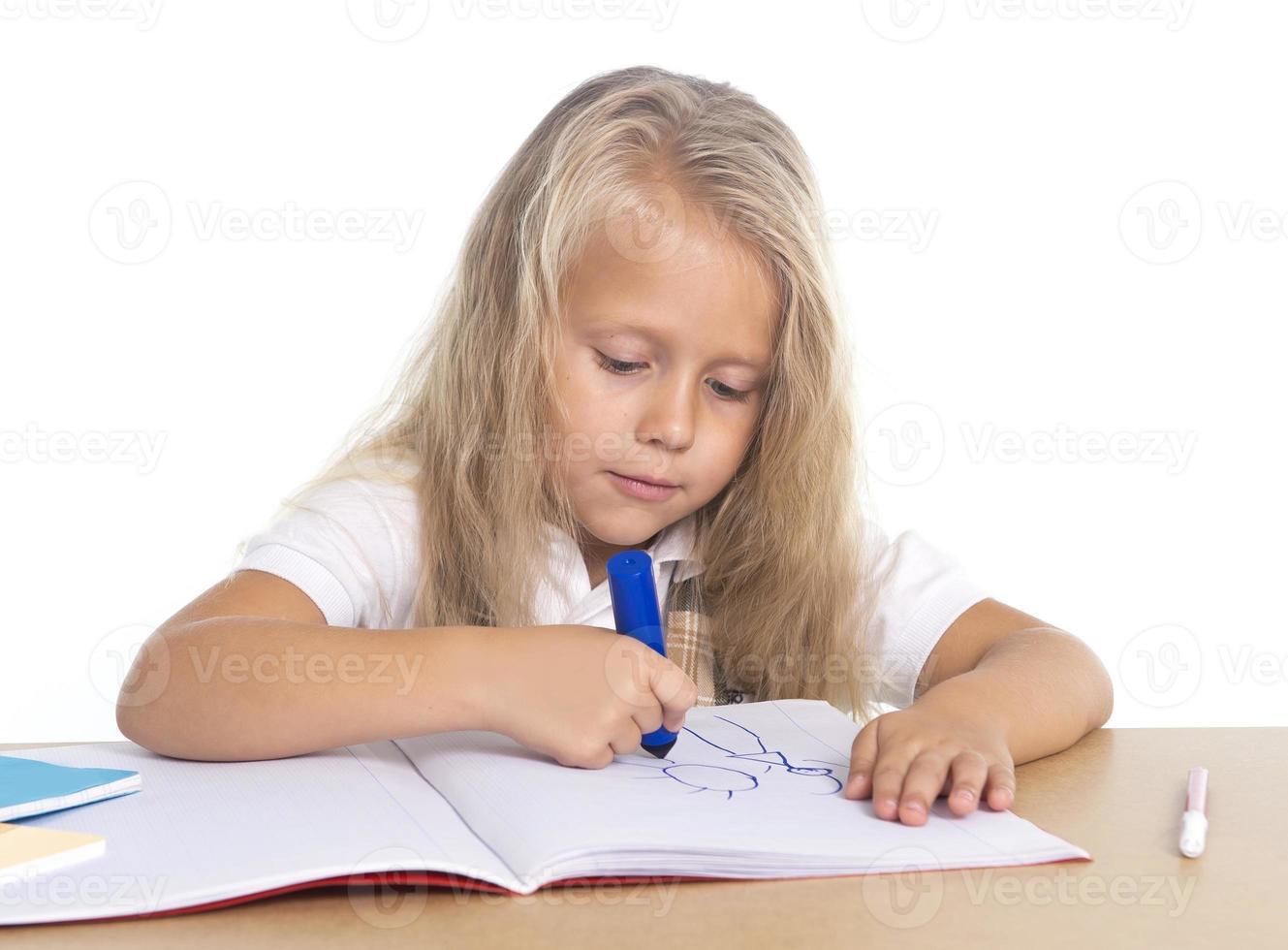 schattige schoogirl gelukkig op bureau puttend uit Kladblok met marker foto