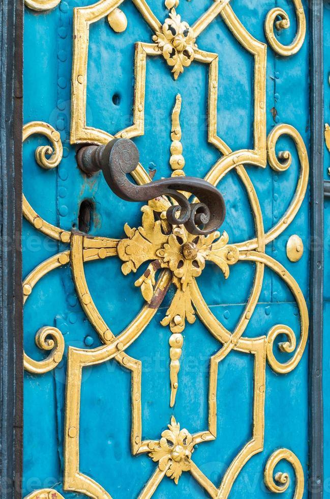 blauwe deur versierd met gouden versiering en handvat foto