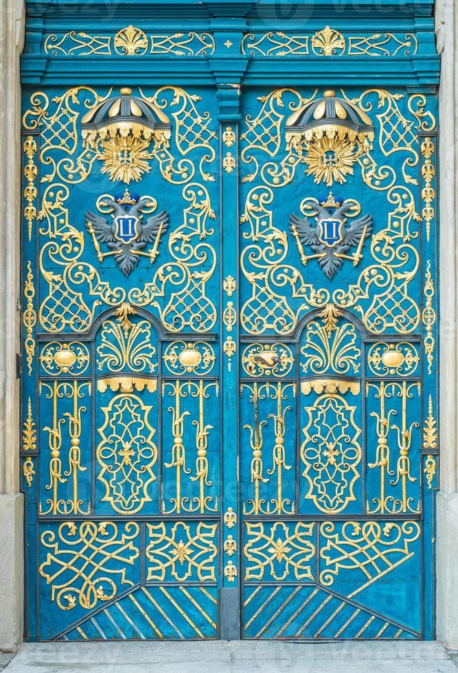 blauwe deur versierd met gouden versiering, ijzeren handvat, stenen portaal foto