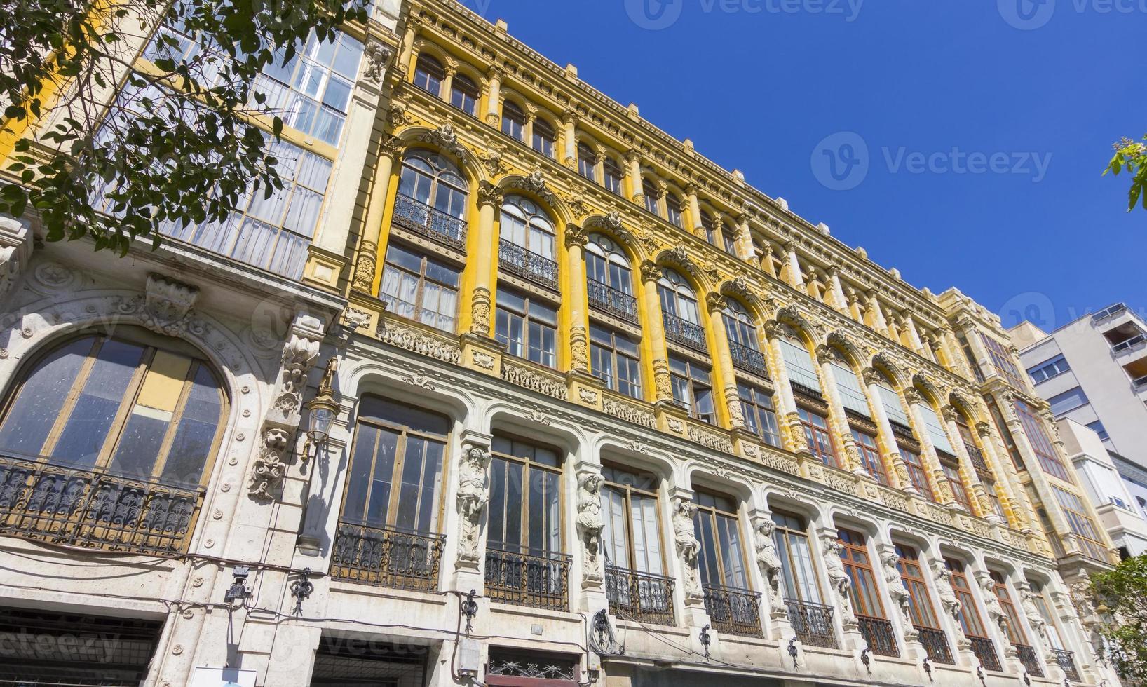 mooi oud gebouw met zeer versierde gevel en grote ramen foto