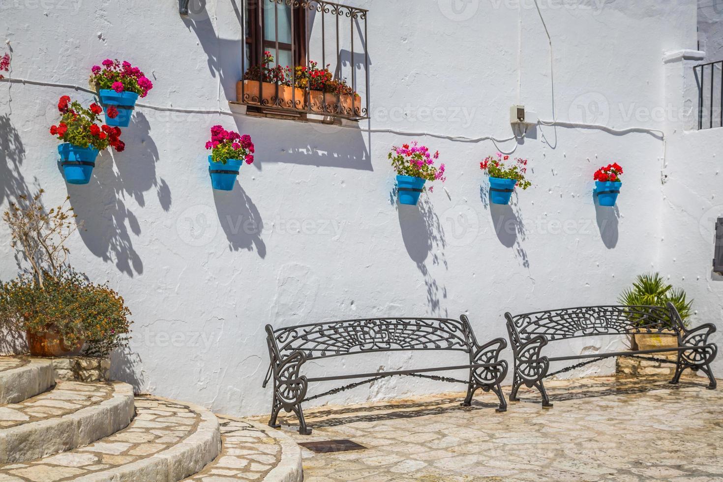 pittoresk straatje van mijas met bloempotten in gevels. andalus foto