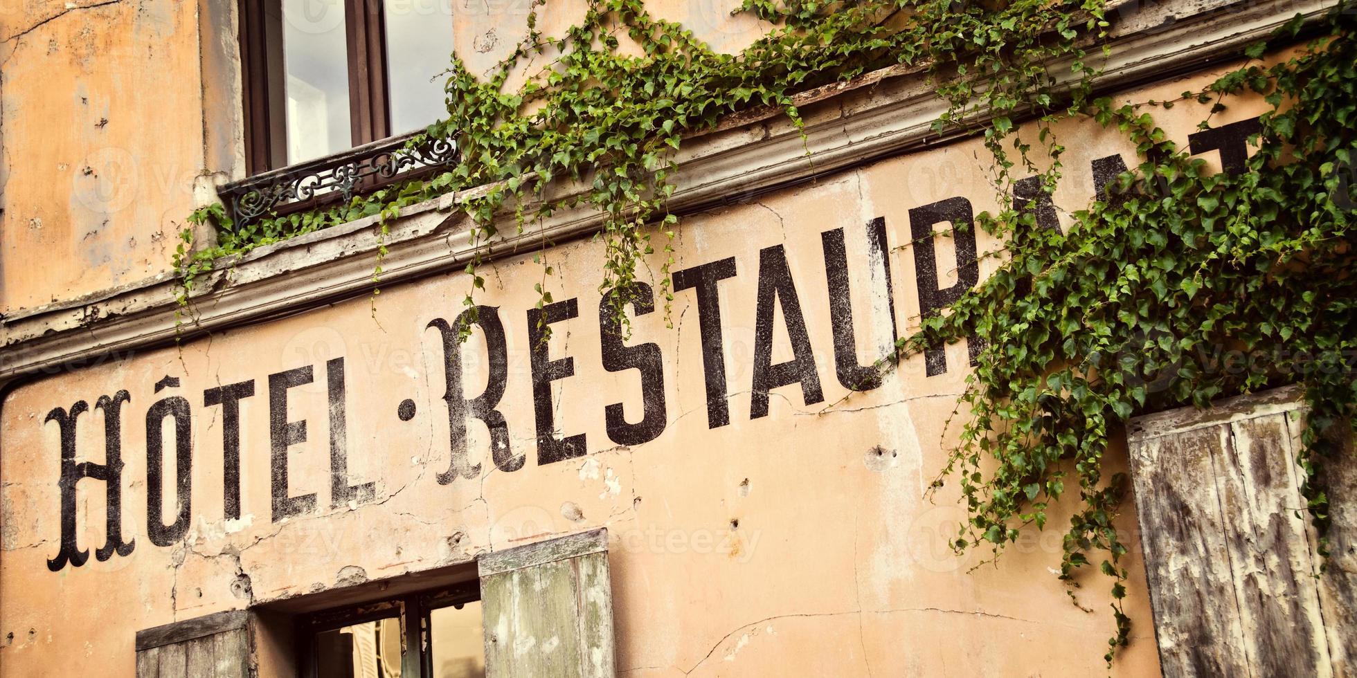vintage Frans hotelteken geschilderd op een oud huis foto