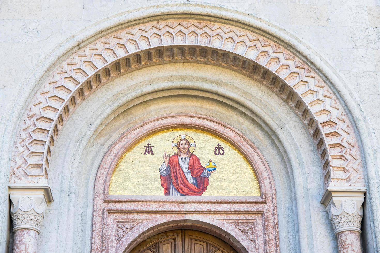 Gods beeldmozaïek boven de deuropening van een kerk. foto