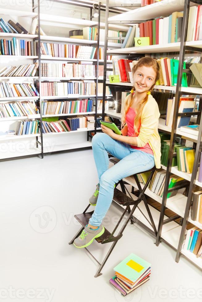 meisje met twee vlechten en tablet zit op de ladder foto