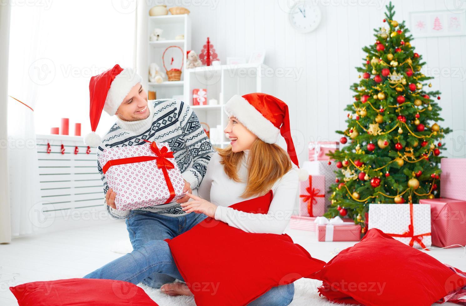 gelukkig gezin paar met een cadeau op Kerstmis thuis foto