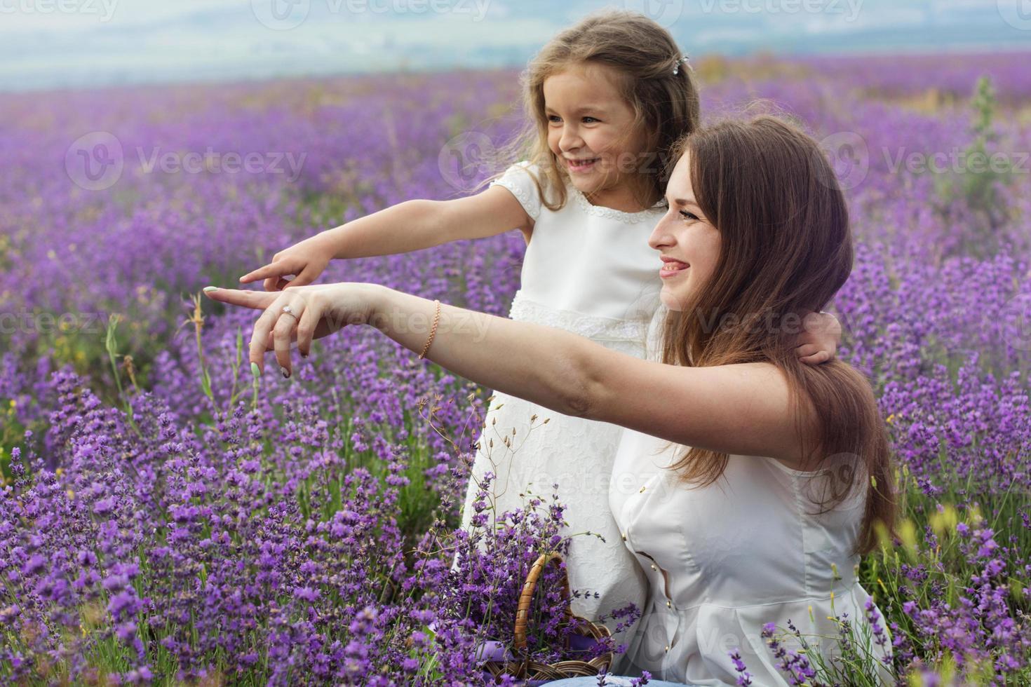 moeder met dochter in lavendelveld houden mand vast foto