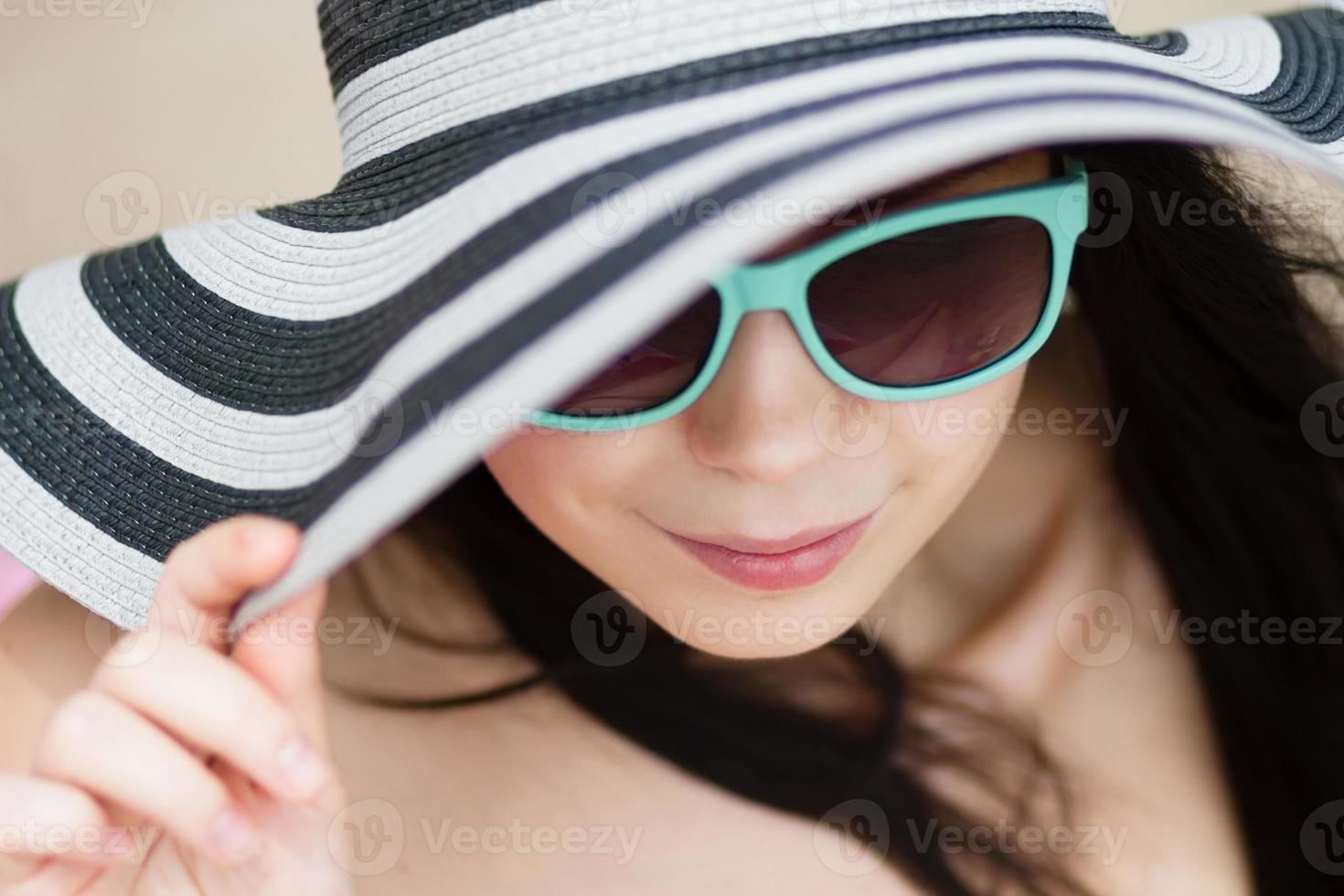 jonge brunette in turqoise zonnebril foto