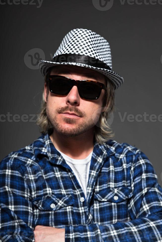 expressieve jonge man met blond haar hoed en zonnebril dragen. foto