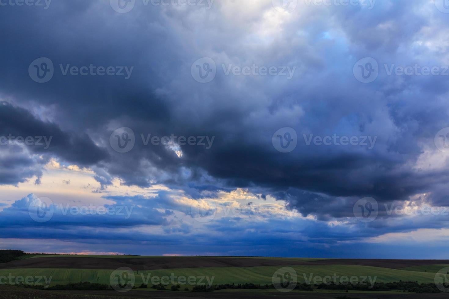 donkere onweerswolken geprofileerd op de avondlucht foto