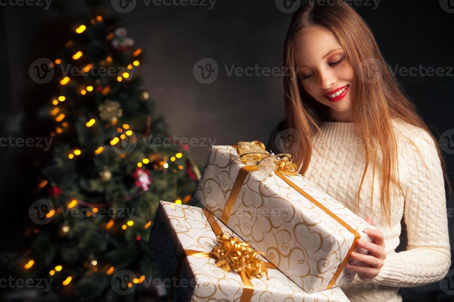 Kerstmis. lachende vrouw met veel geschenkdozen foto