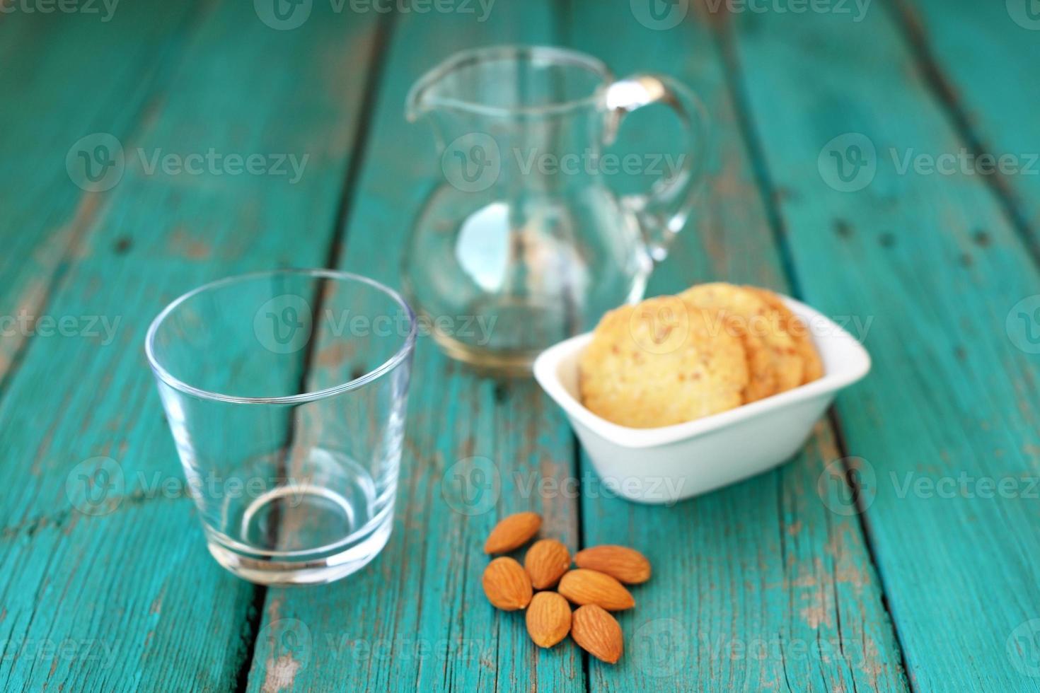 leeg glas met zelfgemaakte amandelkoekjes en hele amandelen foto
