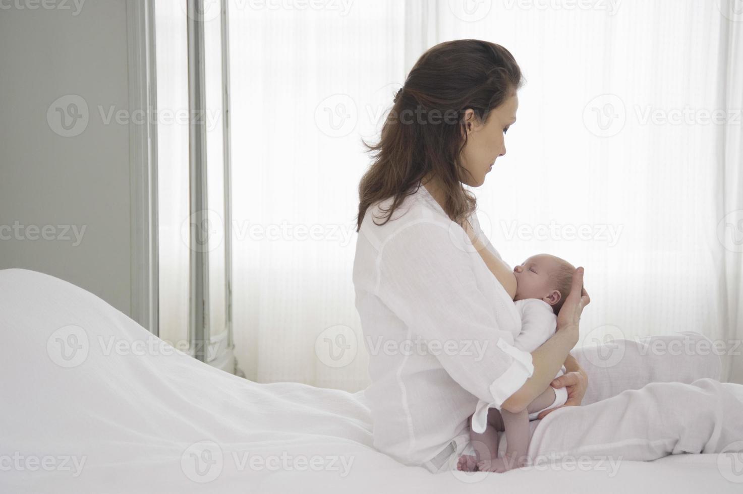 moeder die de pasgeboren baby borstvoeding geeft foto