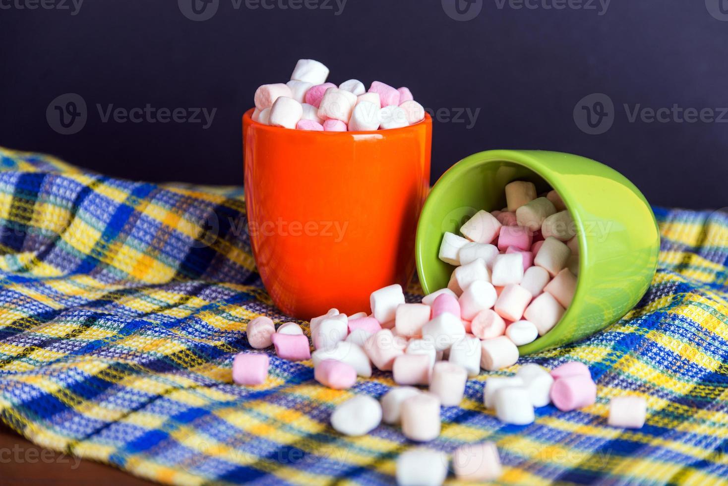 marshmallows morsen uit een groene beker foto
