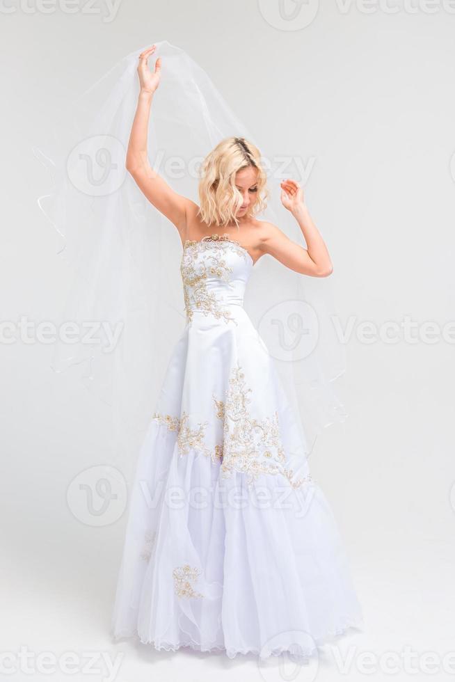 schieten een bruid in een trouwjurk in de studio foto