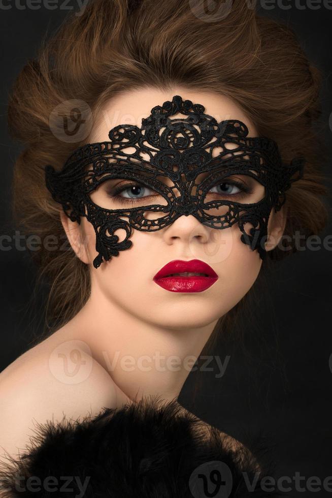 portret van jonge schattige vrouw in zwarte partij masker foto