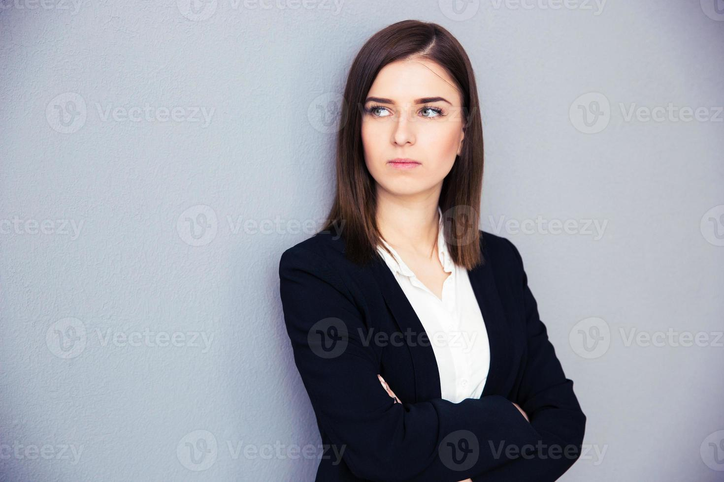 jonge ernstige zakenvrouw met gevouwen armen foto