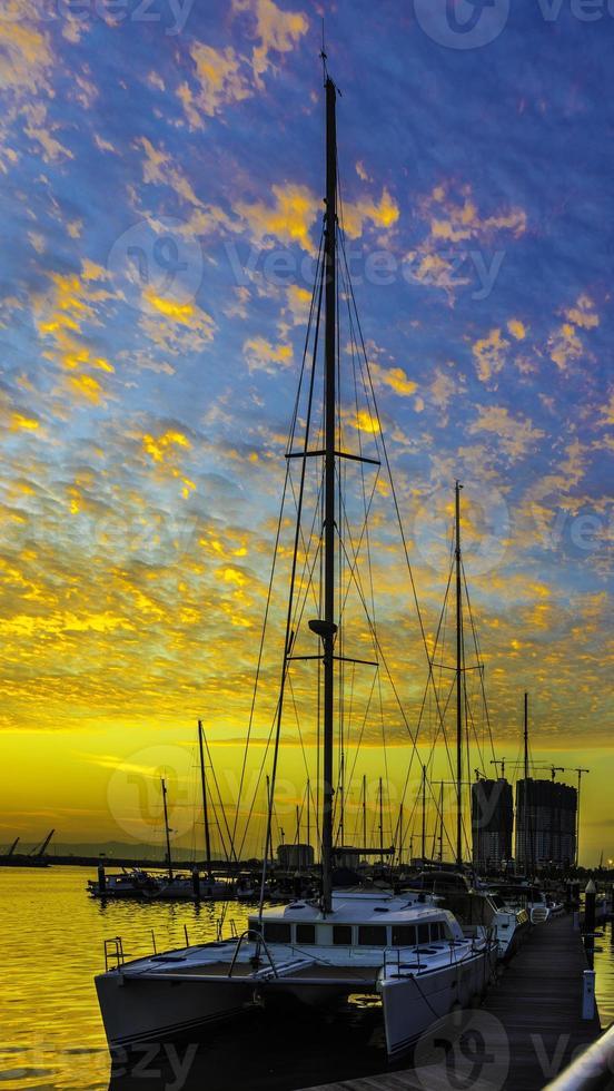 catamaranboten bij pier tijdens zonsondergang foto