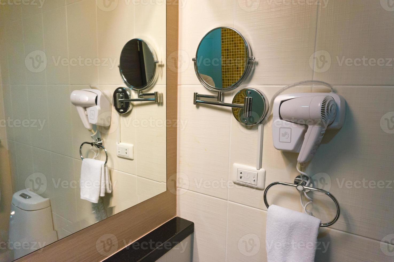 witte föhn en spiegel aan de muur in de badkamer foto