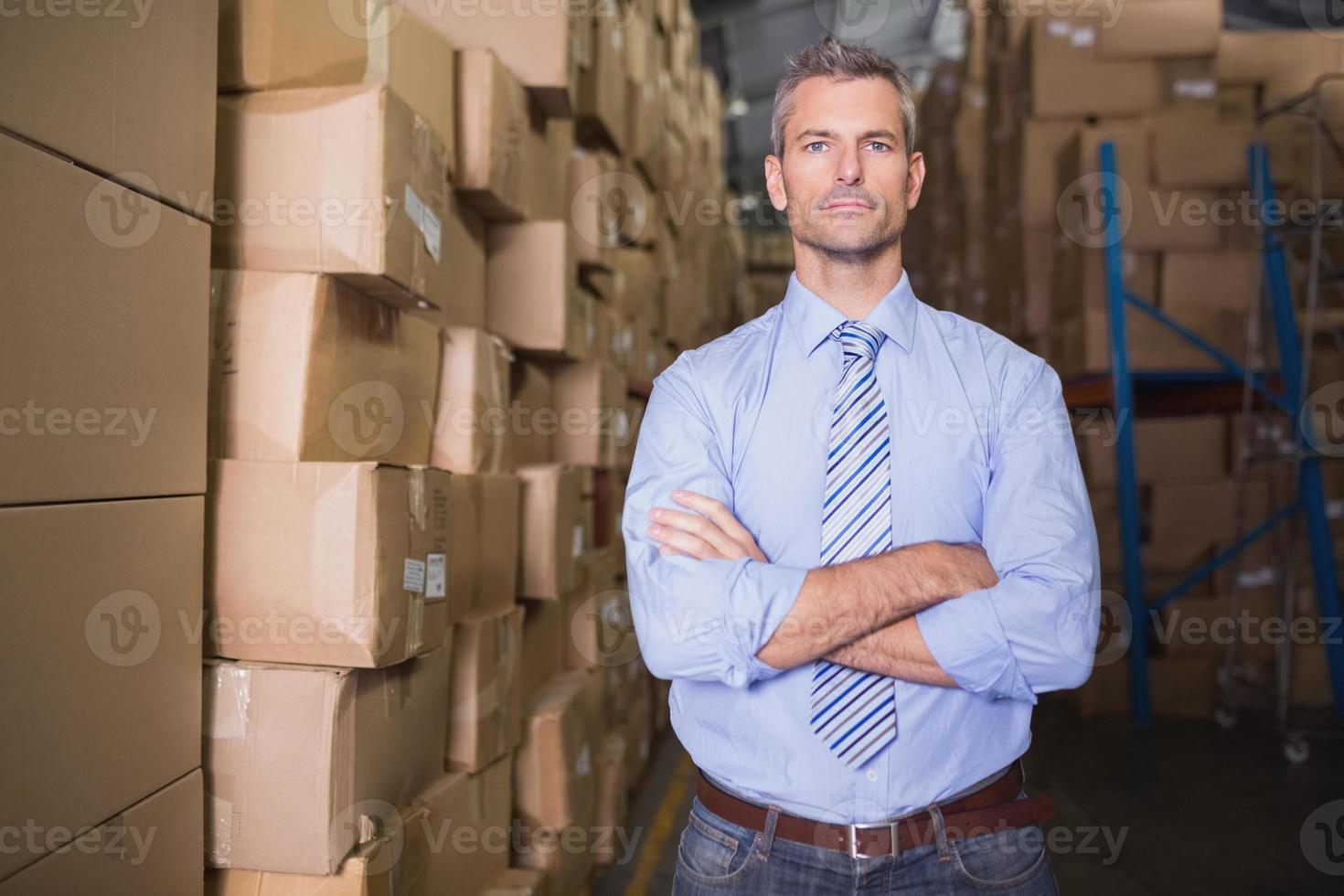 serieuze manager met gekruiste armen in magazijn foto