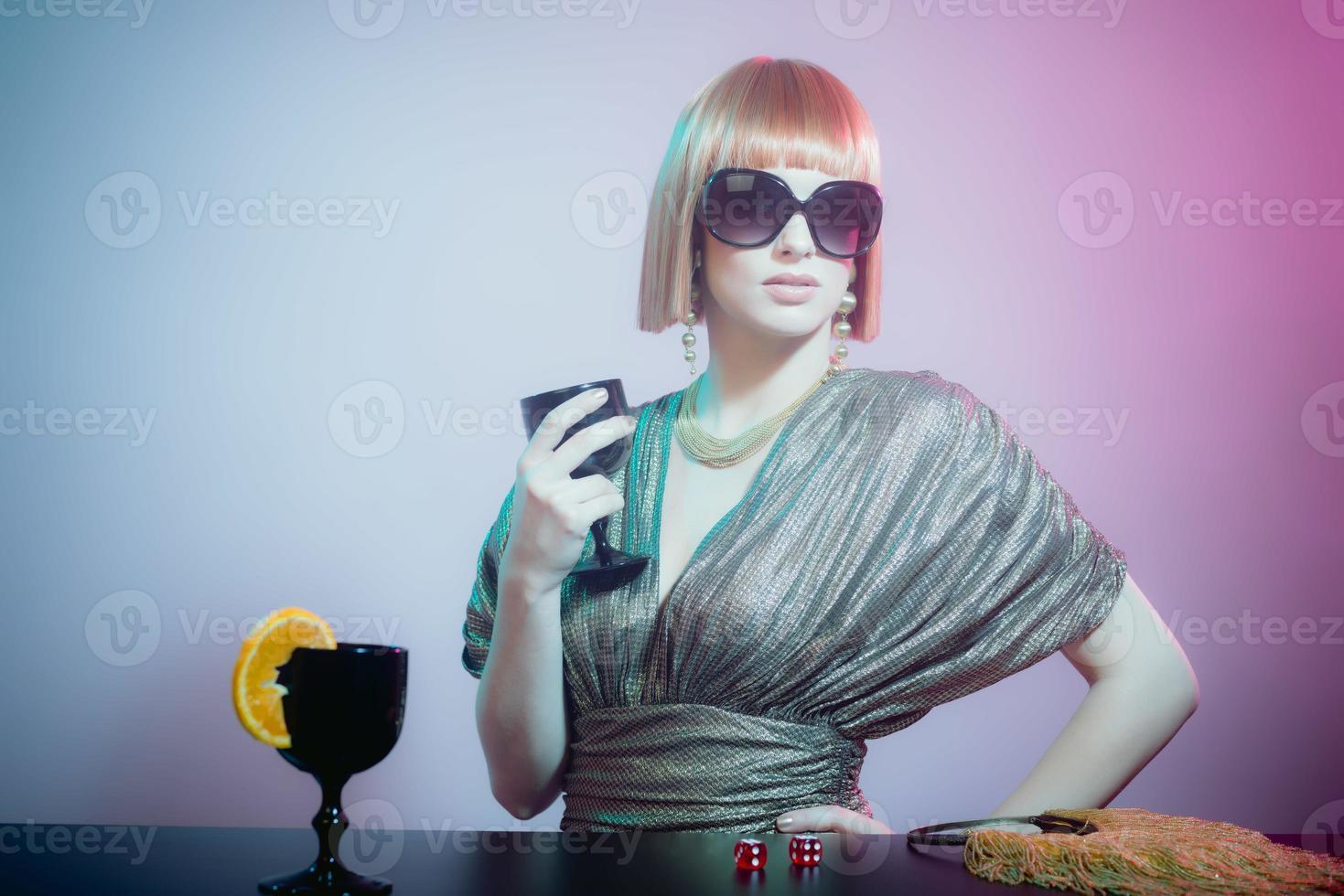 vrouw in zonnebril op bar met wijnglas foto