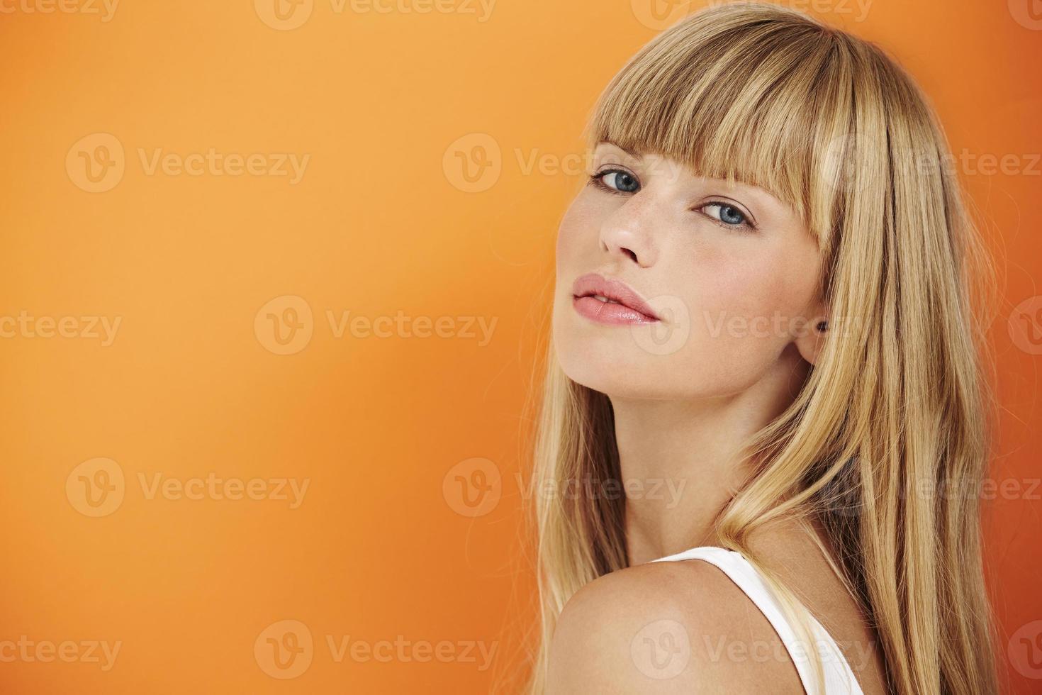 prachtige jonge vrouw op oranje foto