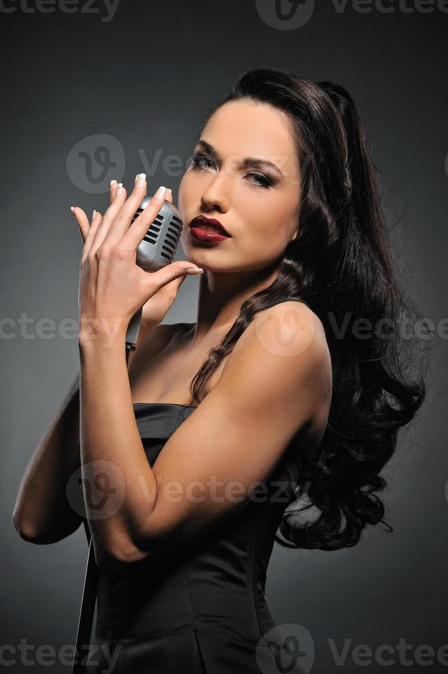 aantrekkelijke brunette vrouw met een retro microfoon foto