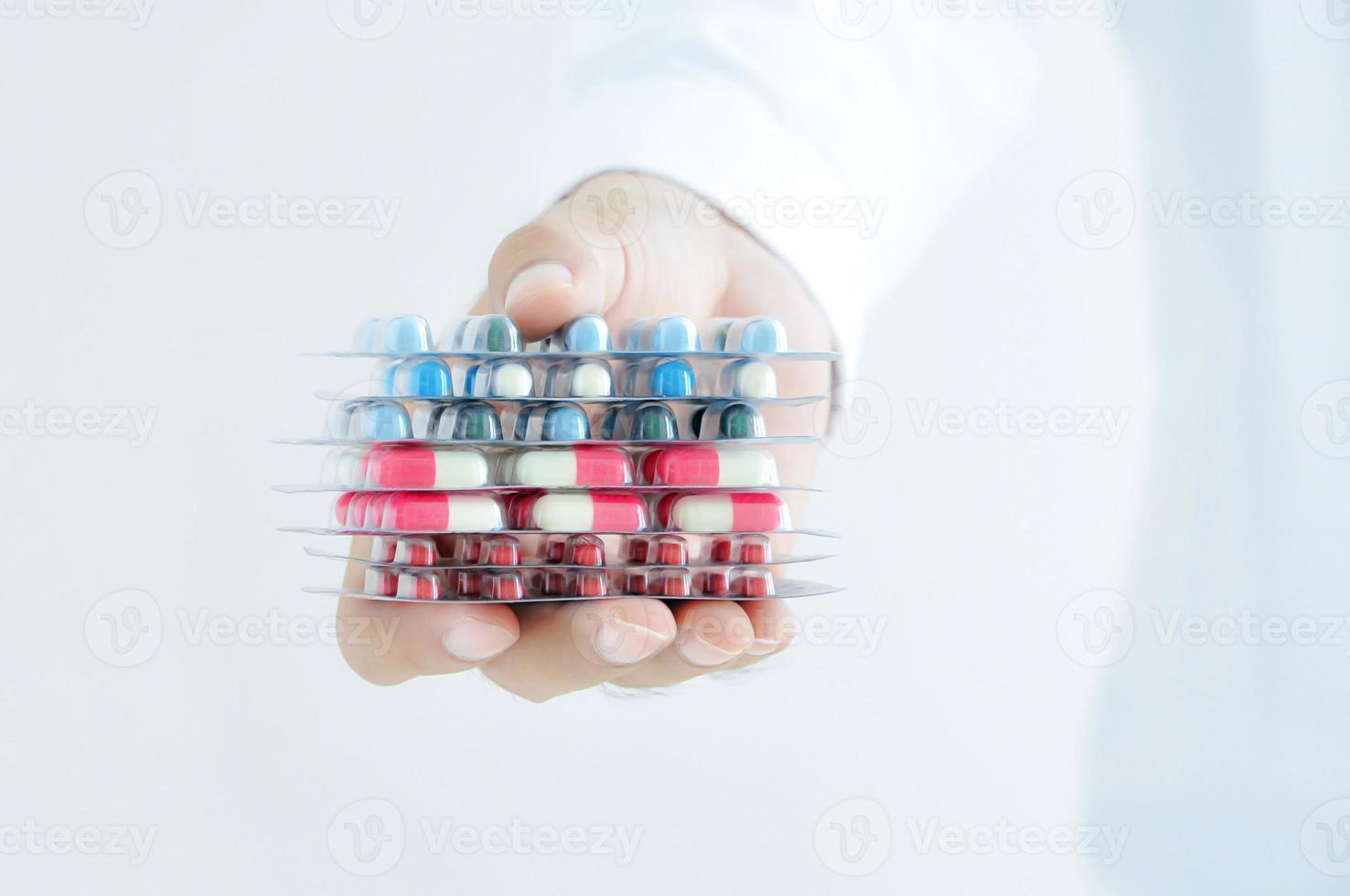 hand die medicijnen geeft - capsules of pillen in blisterverpakkingen foto