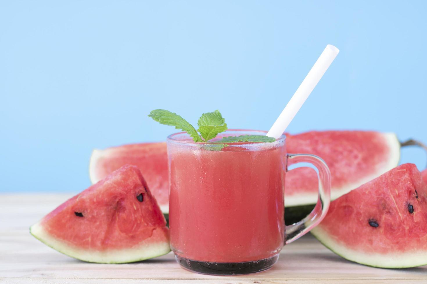 watermeloen drankje en plakjes op blauwe achtergrond foto