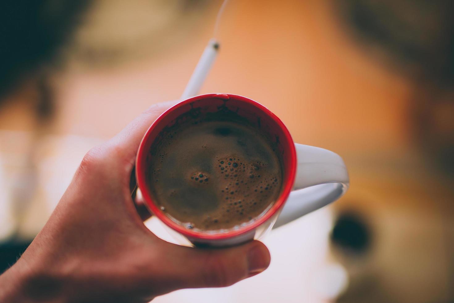 hand met sigaret en koffie in mok foto