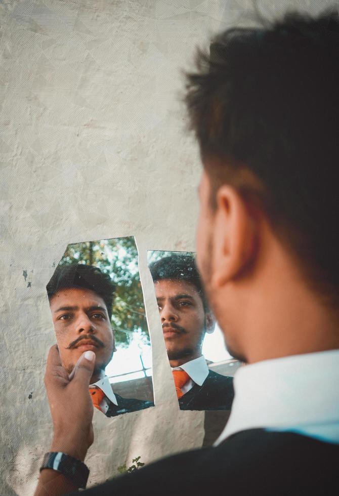 man op zoek in gebroken spiegel foto