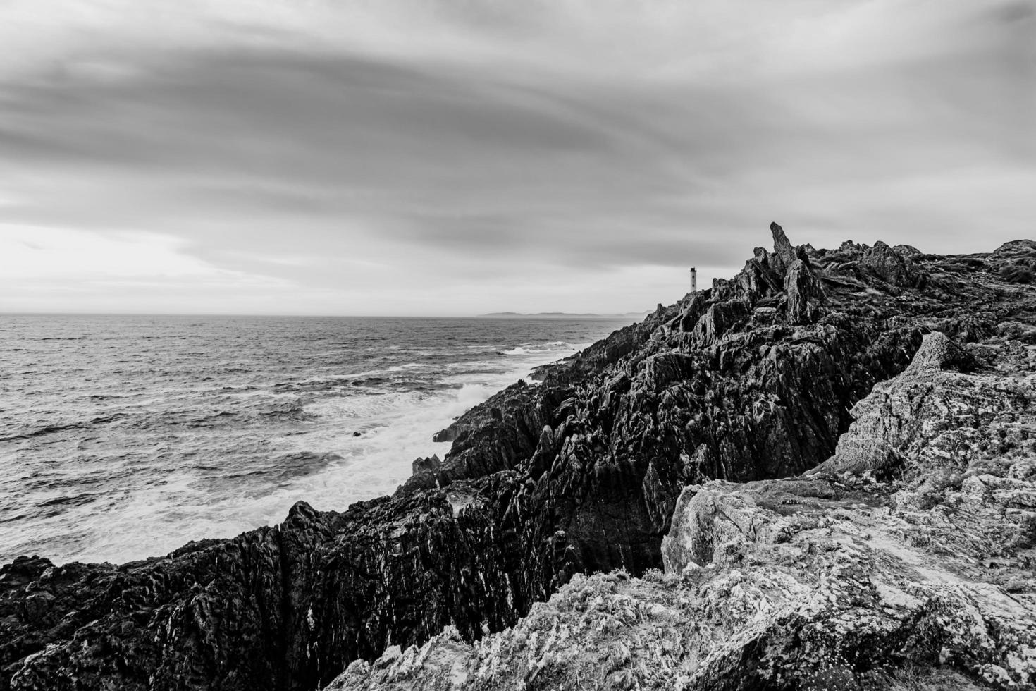 zwart-witte vuurtoren aan de kust foto